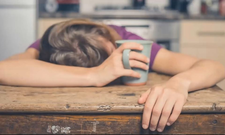 Women with a cup of coffee laying head down on wood table