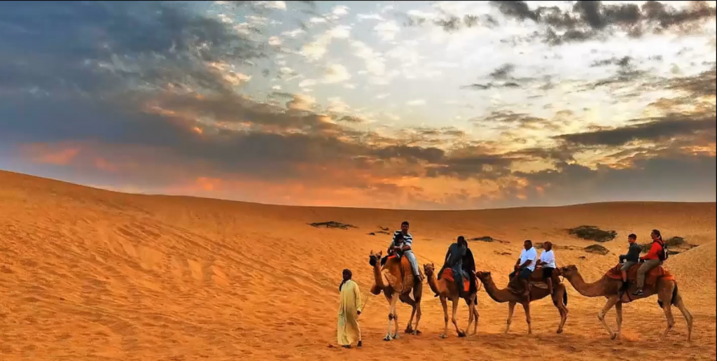 For people moving through the desert, one walking and three on camels.