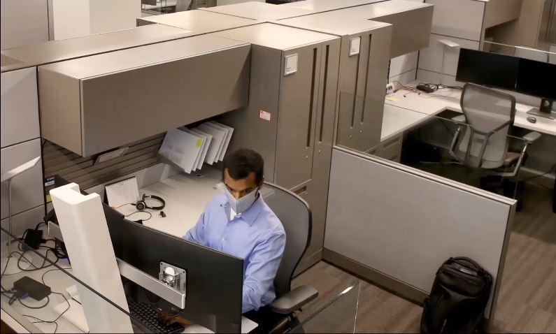 man setting in cubical with mask on
