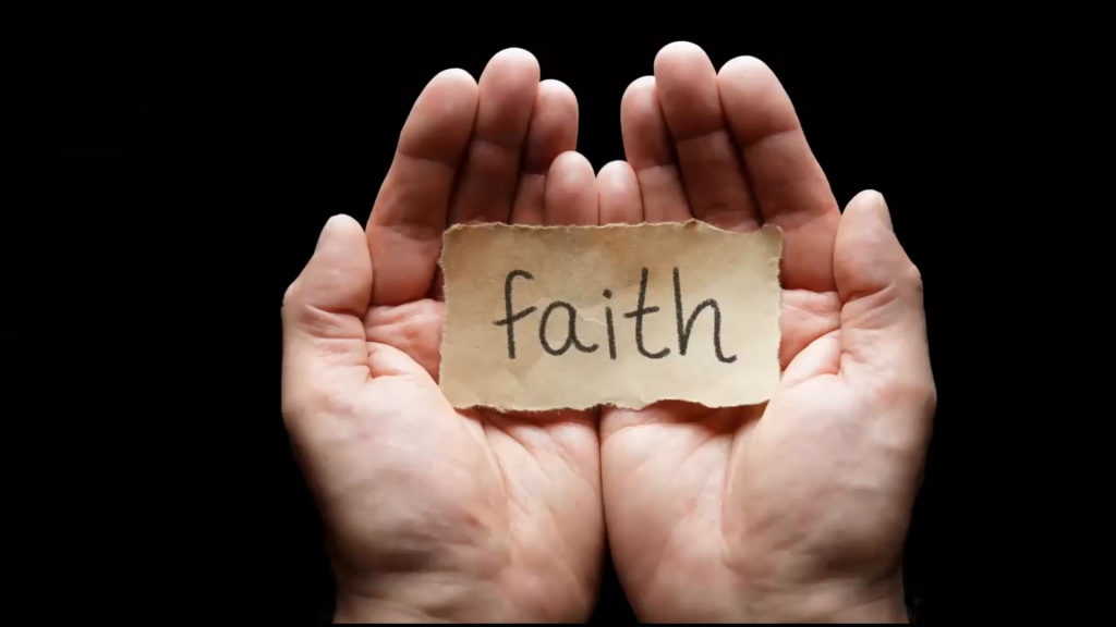 """Hands holding a piece of paper with """"Faith"""" written on it."""