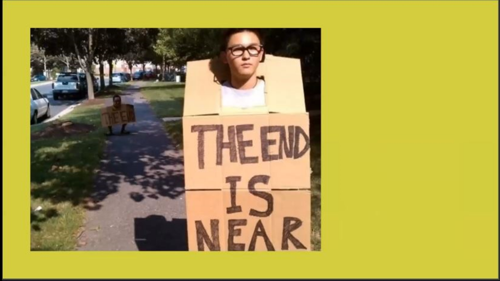 """A woman holding a sign that says """"the end is near."""" A little behind here a man holds a sign that says """"the end."""""""