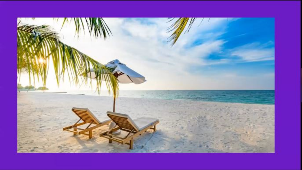 Lounge chairs under an umbrella on a beach.